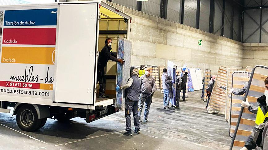 Sacando colchones y somieres del camión de Muebles Toscana