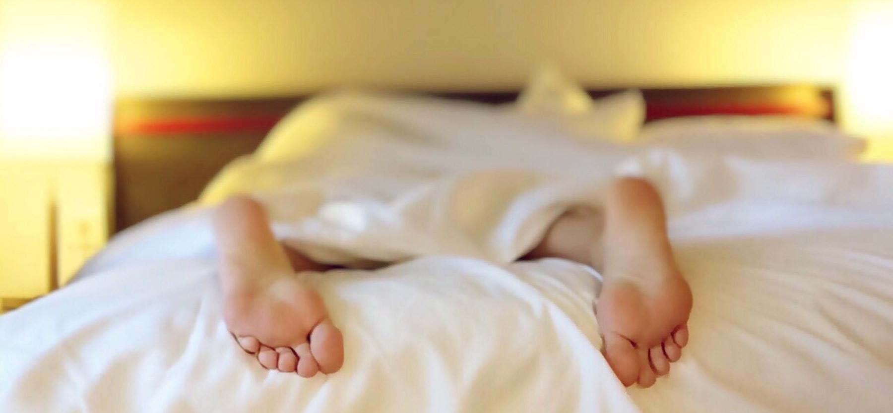Pies de adolescente saliendo de la cama